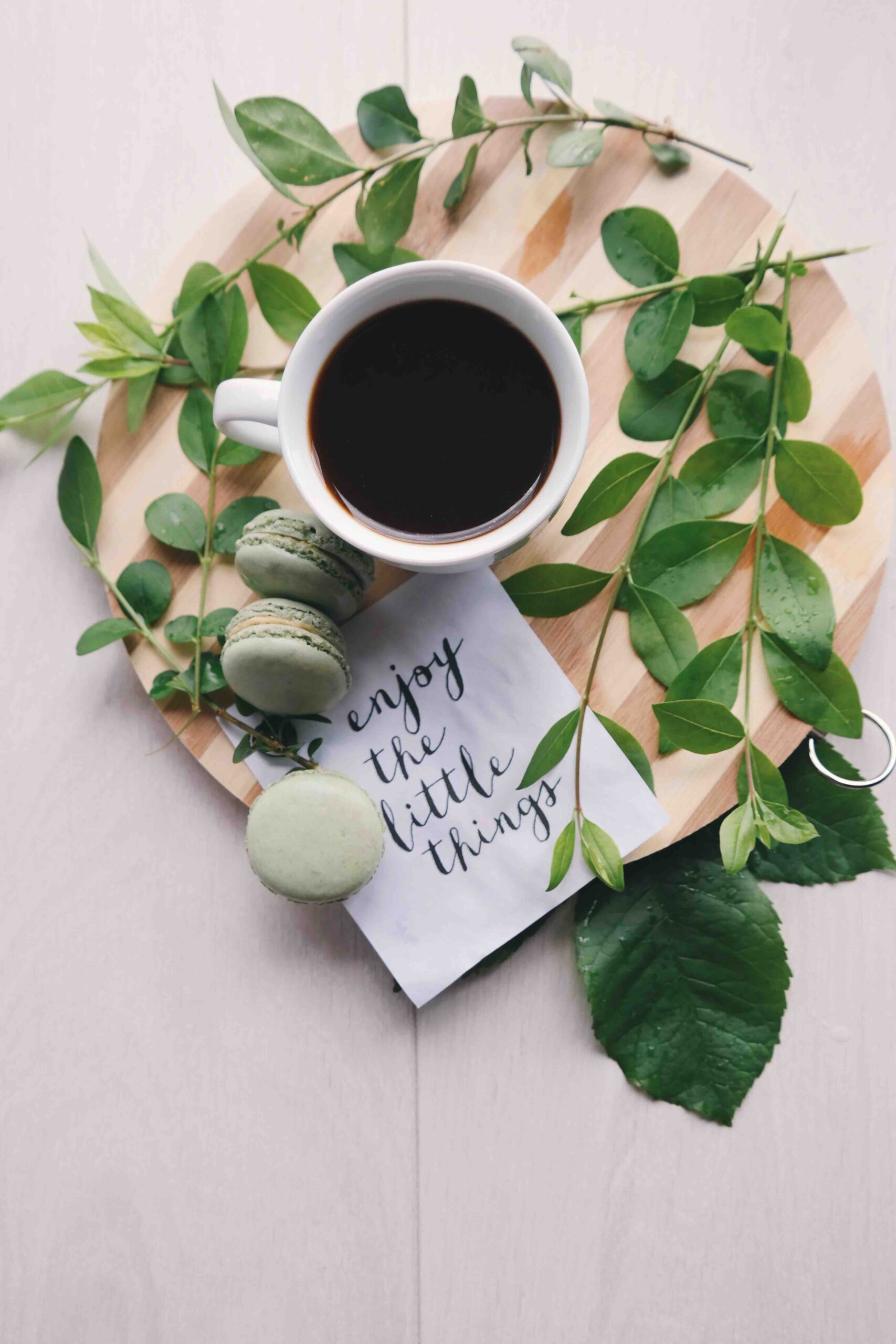 black coffee on a wooden board with leaves around and green acaroons next to a piece of paper with itallic writing enjoy the little things