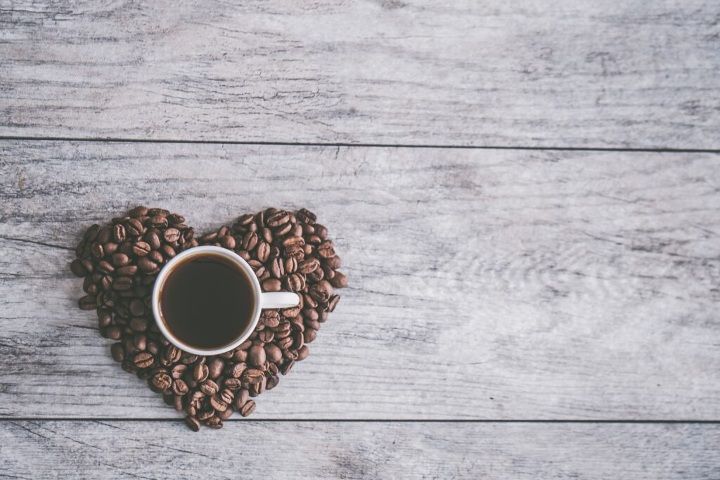 black coffee on a wooden background with heart shaped coffee beans around the white cup