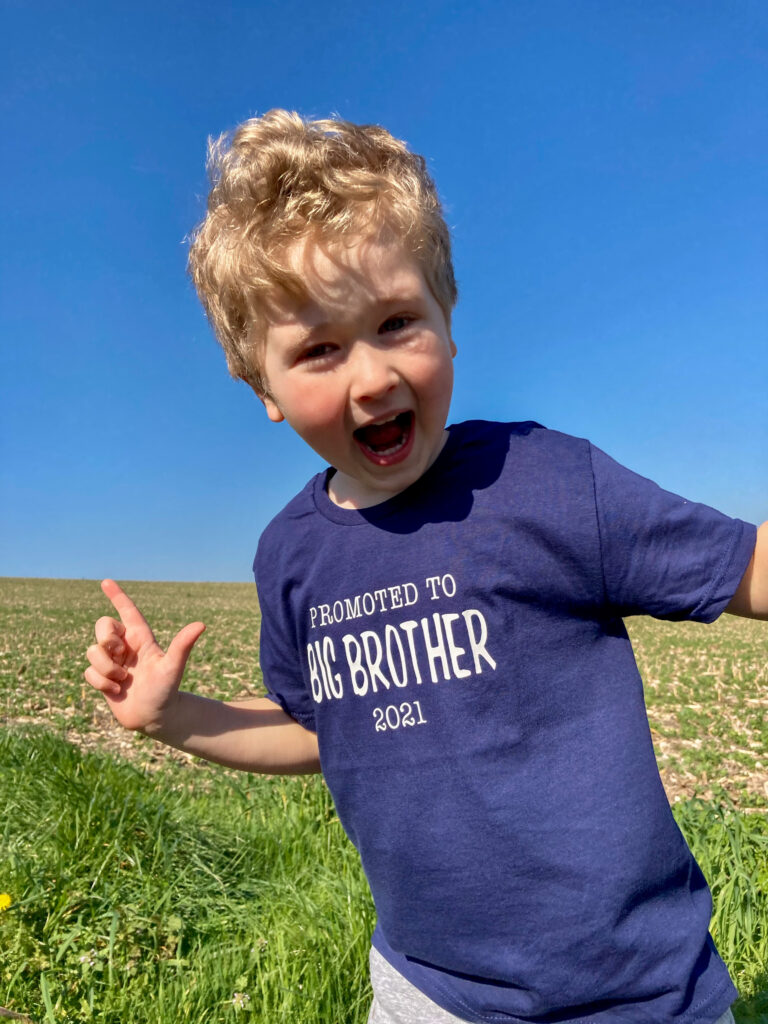 Lucas smiling with his mouth wide open wearing a navy Tshirt saying promoted to big brother