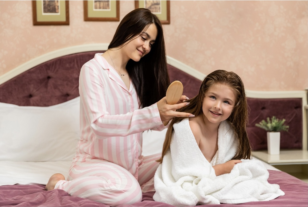 Mum and daughter sat on the bed. Mum brushing hair of daughter