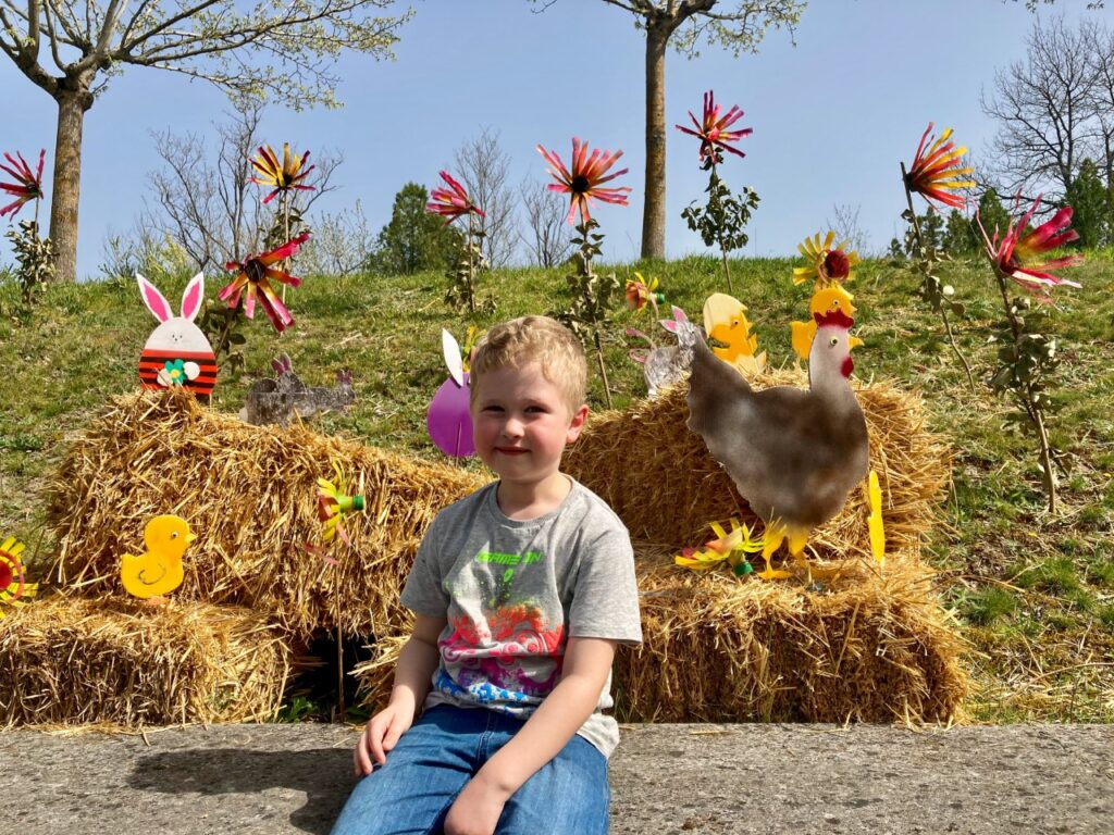 Lucas sat with hay bales and statues of flowers, chickens and bunnies behind him