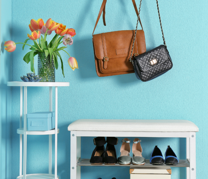 storage solutions for the front door, handbags are hung up on the wall. Shoes are on a shoe rack that can also be sat on