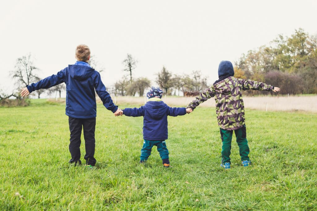 three children stood in a field holding hands with their arms outstretched wearing winter outdoor clothes