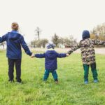 three children stood in a field holding hands with their arms outstreched, they are wearing outdoor winter clothes