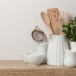 kitchen counter with white pots and jugs holding utensils