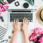 a laptop with a ladies hands typing. there are flowers, make up and jewellery around the laptop