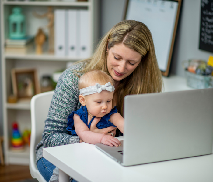 a ;ady working at a laptop holding a baby