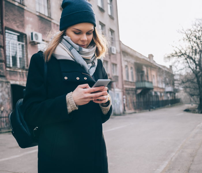 a lady stood by the side of a road looking at her phone, wearing a black woolen hat and coat with a grey scarf
