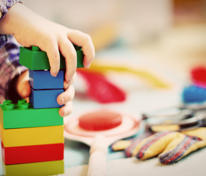 a childs hand can be seen playing with colourful building blocks