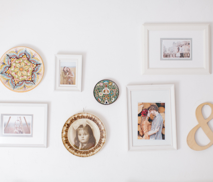 pictures in an array of frames hung on the wall