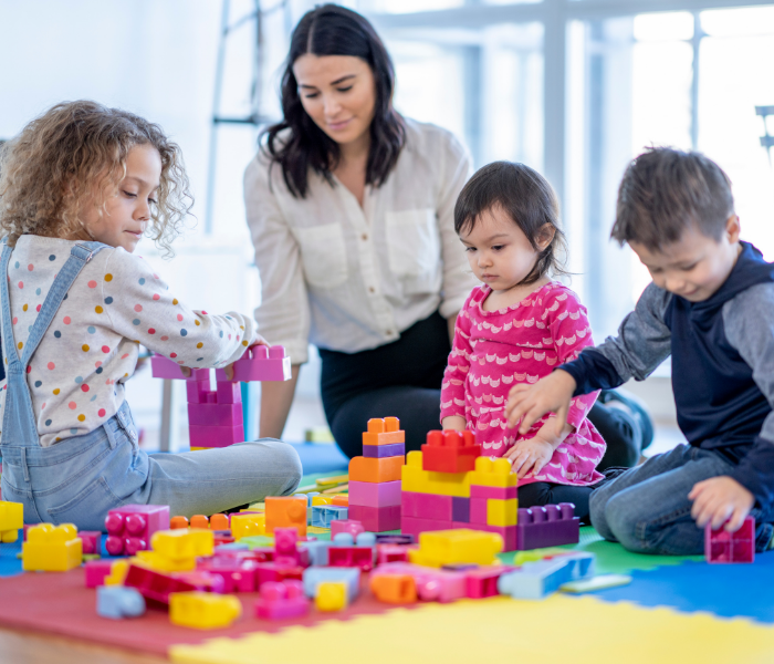 a lady in a childcare setting with children playing with blocks, a career in childcare